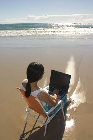 Casual woman with laptop at the beach
