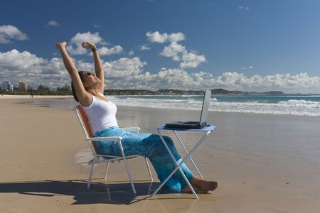 expressing: Woman with laptop expressing her happiness at the beach