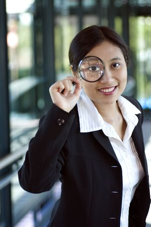 salesgirl: Asian businesswoman with magnifying glass Stock Photo
