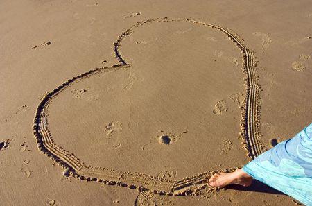 femme dessin: Une femme, un coeur de dessin sur le sable