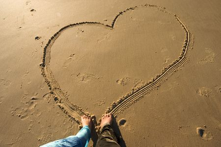 adore: Couple drawing a heart on the sand