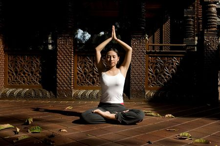 traditional house: Asian woman meditating in front of asian traditional house