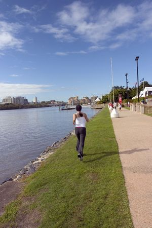 striving: woman jogging by the city river