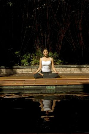 freed: Asian woman meditating by the pond Stock Photo