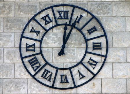 Clock with roman figures on a textured wall photo