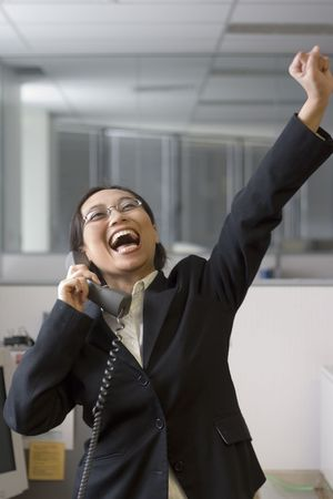 Excited businesswoman in her office Stock Photo