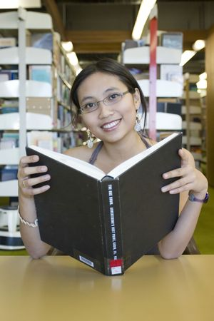 assignments: Asian woman reading in the library Stock Photo