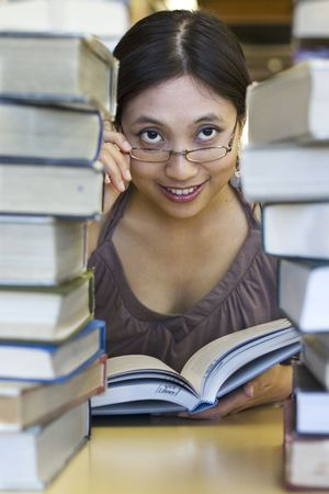 Attractive Asian student reading behind the books Stock Photo - 240161