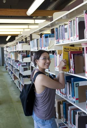 Asian student looking for books in a library Stock Photo - 240155