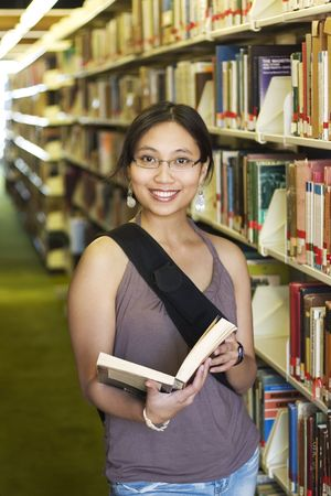 Student in a library holding a book Stock Photo - 240148