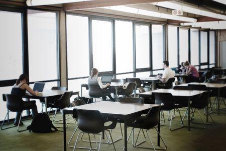 scholars: Personas estudiar en la biblioteca, se centr� en la segunda ni�a (el uno en el centro)  Foto de archivo