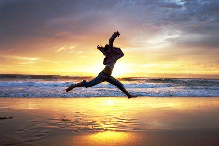Woman jumps at sunrise