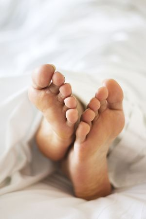 Womans feet under the blanket photo