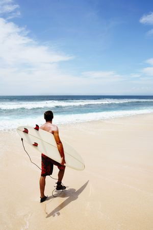 dreamland: Young man going to surf at Dreamland, Bali Stock Photo