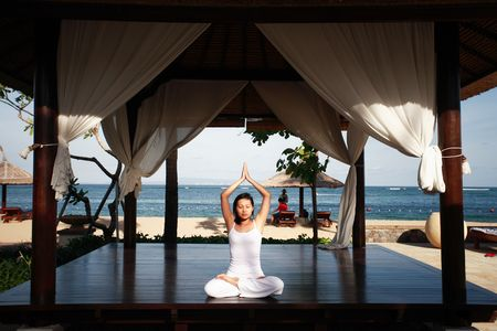 Asian woman meditating at the hotels gazebo photo