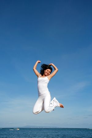 Attractive asian woman jumping at the beach photo