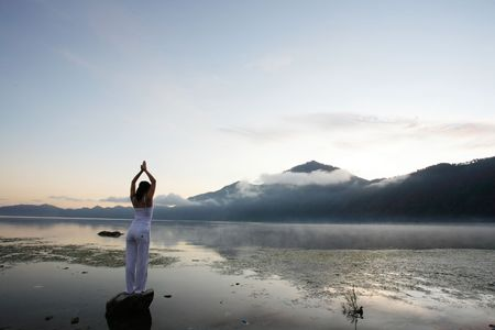 foggy hill: Woman meditating at lake by a mountain