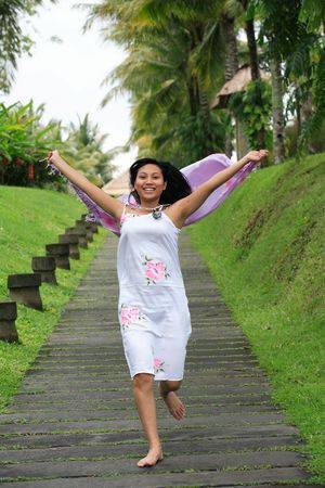Beautiful Asian woman running with her sarong in a garden photo