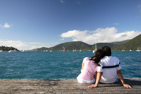 retreat: Asian couple enjoying the beautiful sea landscape while sitting on a piece of wood