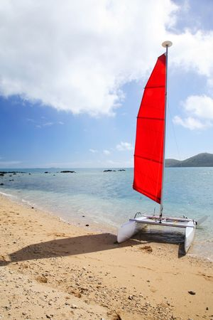 Red sailing boat arrived on a beach Stock Photo - 665283