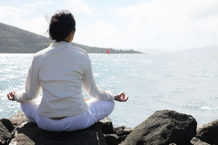 weekend break: An Asian woman practices Yoga with beautiful landscape of mountains and sea