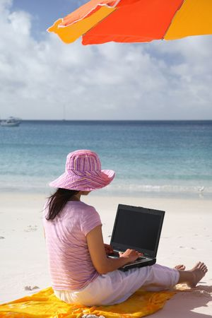 Asian woman with pink hat working on the beach in Queensland, Australia Stock Photo - 665292