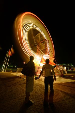 a couple watching ferriswheel spinning during festival in Brisbane, australia photo