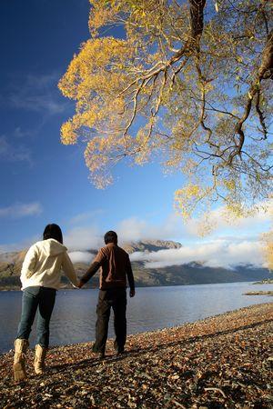 asian travel: Lake and a couple walking enjoying beautiful view of New Zealand mountains