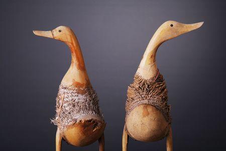 Wooden ducks shot over gray background photo