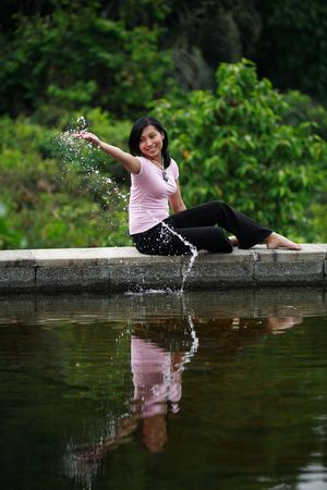 Attractive Asian woman playing with water. photo