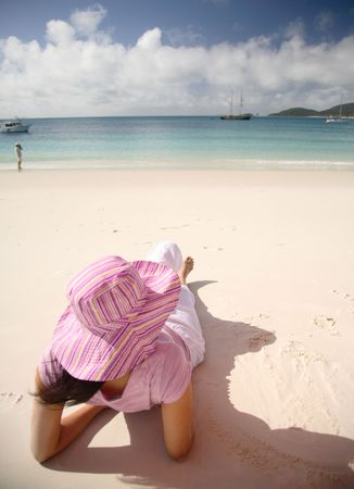 whitsunday: A woman relaxing on the beach in Whitsunday island