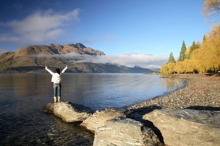 lost lake: Victorious woman standing at New Zealand Lake, Queenstown Stock Photo