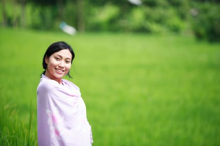 Asian woman with her sarong at rice field shot with shallow DOF photo