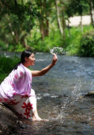 Asian woman playing with water in a village photo