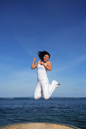 Attractive asian woman jumping on a beach Stock Photo - 744136
