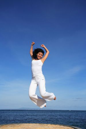 Attractive asian woman jumping on a beach Stock Photo