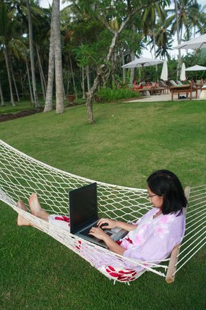Asian woman working on her vacation at the beach photo