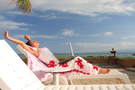 mobility: Asian businesswoman working on her vacation at the beach Stock Photo