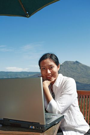 Asian woman working at a restaurant with a mountain in the background. photo