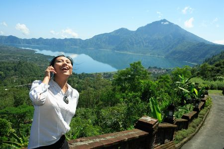 call of nature: Asian woman laughing while making a phone call