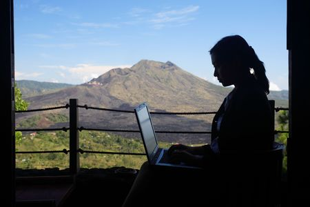 Silhouette of business woman working with a mountain in the background photo