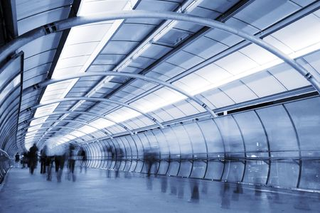 Business People walking in a futuristic tunnel. Shot with slow shutter speed to create blur effect photo