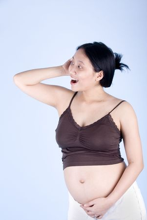 Studio shot of a pregnant woman chatting on the phone over blue background with her stomach exposed photo