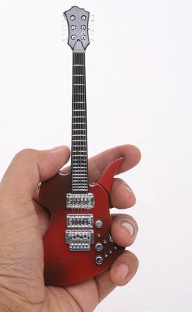 strat: Isolated miniature of red electric guitar held by a hand over white background Stock Photo