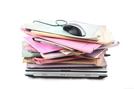 Isolated stack of folders with laptop computer and a mouse shot over white background photo