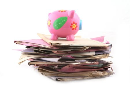 manage clutter: Isolated stack of folders with piggy bank at the top shot over white background