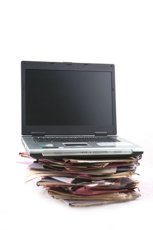 manage clutter: Isolated stack of folder with laptop computer shot over white background