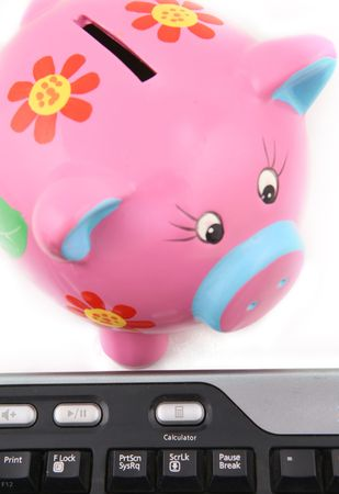 Isolated keyboard and Piggy bank shot over white background. Image focus on the keyboard photo