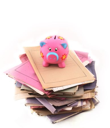 manage clutter: Isolated stack of folders with piggy bank on top shot over white background Stock Photo