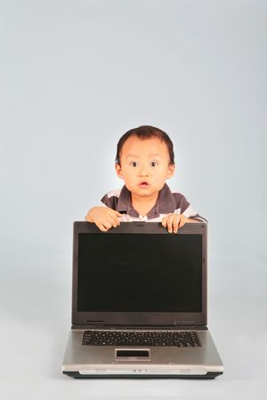 A shocked toddler behind a laptop computer with a blank screen. Eyes are wide open Stock Photo - 3438789